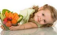 bambina stradaiata per terra con in mano un contenitore con frutta e verdura