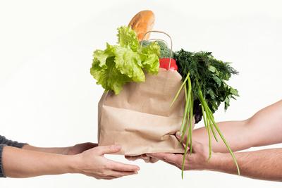 sacchetto della spesa che viene porto ad una persona con due mani stese