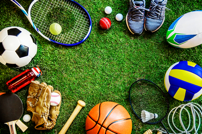 racchetta da tennis, scarpe da ginnastica, palla da calcio, palla da basket, racchette da pin pong ed altri attrezzi sportivi posti su un'area verde