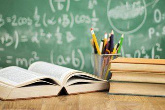 libro aperto su una cattedra e portamatite con matite e penne