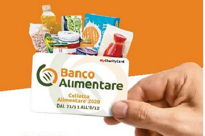 card con scritta Banco Alimentare Colletta Alimentare dal 11/11 all'8/12 tenuta in mano. Sullo sfodo, dietro la card immagini di prodotti alimentari
