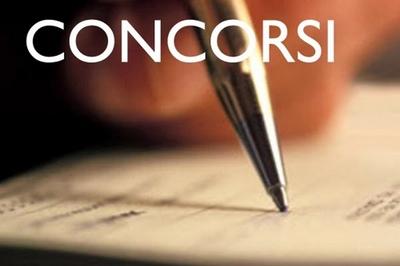 scritta concorsi con una mano che impugna una penna nell'atto di scrivere