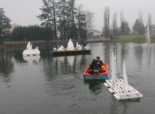 una barca raggiunge il centro del lago trasportando alcune sagome del presepe