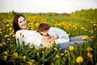 Una mamma in un prato fiorito con in braccio un bambino