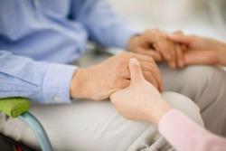 persona che tiene tra le sue mani quelle di una persona anziana