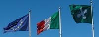 Foto bandiere Europa, Irtalia e Lombardia con cielo azzurro