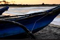 immgine di due piroghe sulla riva di un fiume